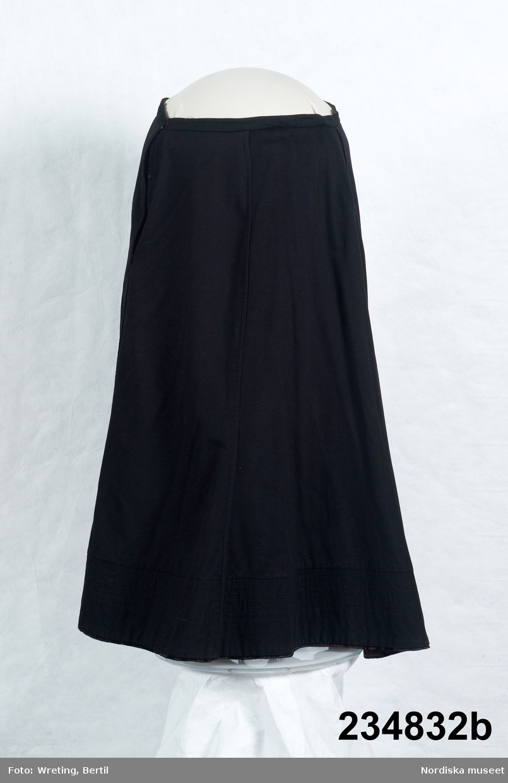 """Huvudliggaren: a-b Klänning, bestående av liv och kjol; kjolen av svart kläde, livet 'koftan' av svart ylle i satinbindning. Koftan har dek. veck, applikationer och snörmakeri.""""  A. Liv av svart yllekypert,  typ cheviot,  i modesnitt från omkr. 1900. Sytt på foderstomme av  mönstertryckt bomullssatin i ljusbrunt och vitt, med  12 insydda stålfjädrar fördelade runtom. Midjekort med 2 framstycken med blusande vidd genom nedsydda veck från axeln som öppnar sig över bröstet och hålls ihop vid midjan.  2 breda veck i framkant döljer knäppning med 2 svartlackerade hakar och hyskor, dekor på vecken av  2 svarta silkeagraffer med hängande snörmakerier. Ståndkrage som sluter till kring halsen och knäpps vid vänster sida med hakar och sydda trådhankar. 3 ryggstycken med en snibb mitt bak. Knäppning med hakar och hyskor även i foderlivet.  Något svängda ärmar med 2 sömmar, lätt rynkade på ärmkullen, dekorerade med 3 partier med tvärgående stråveck och i nederkanten applikatioer av svart siden sydda med  smala snoddar  i konturerna. Mitt bak ett avlångt metallspänne att fästa mot kjolen, stämplat:"""" Patent 7556"""". A.Kjol av svart  tuskaftat klädesliknande halvylle ( fel i huvudliggaren, ej äkta kläde).  Slät upptill, sydd med 3 utsvängda framvåder och 2 bakvåder som är något längre mitt bak. Sömmarna sydda som fällsömmar vilket gör dem något upphöjda, i nederkanten  7 rader maskinstickningar som ger en viss stadga. 2 cm bred midjelinning med långt sprund i vänster sida knäppt med 2 svartlackerade tryckknappar samt 2 hakar och hyskor. Dold ficka i sprundet. Kjolen helfodrad med tunn svart bomullslärft och skodd med 13 cm av ett annat något grövre bomullstyg. I kanten slitband med tät kort lugg av ylle. Klänningen huvudsakligen maskinsydd, sömmerskearbete. /Berit Eldvik 2011-06-08"""