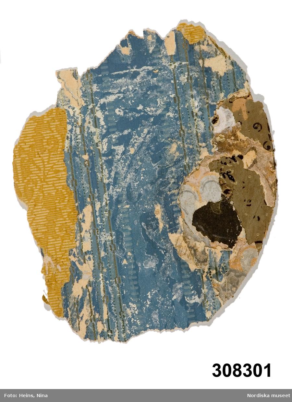 """Huvudliggaren: """"Tapet, prov, papper; lager; överst blå med vattrade bårder och guldlinjer. Mått ca 21 x 17,5 cm. Från Kv. Mercurius, Köpmang. 12 /Oskarshamn/; uppmätning och byggnadsbeskrivning i arkivet. Kulturhistoriska undersökningar, Nordiska museet, Stockholm.""""  Katalogkort: """" Ca 21x17,5 cm. Provbit med lager. Överst blå tapet med vattrade bårder och guldlinjer. AT (=Annika Tyrfelt) 1981.""""  Påskrift """"Prov (o) Derrska gården"""" (något otydligt) med grönt bläck på baksidan. Anm.: Reva, hål. /Marie Tornehave 2007-09-04"""
