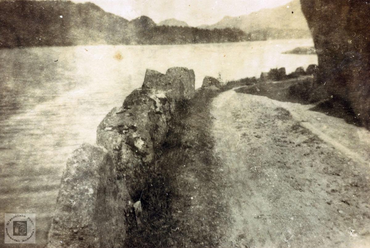 Gamlevegen med stabbesteinar langs vannet.