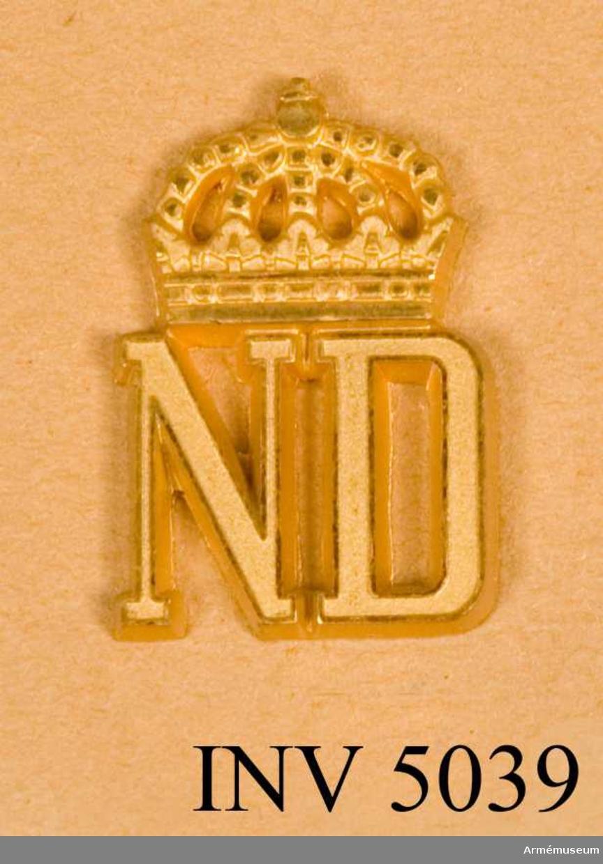 Förbandstecken m/1961, Norrlands dragoner.Tillverkat av metall och i metallfärg m/1960 guld.Till uniform m/ä hade regementet som förbandstecken bokstäverna NDR under kungl krona. Till övriga uniformer förbandssiffror. Före 1928 hade regementet nummer 8, men erhöll detta år nummer 4 i samband med att Smålands husarregemente indrogs. Den 11 juli 1957 fastställdes nytt förbandstecken. Det blev en återgång till det gamla tecknet men medtogs inte bokstaven R enär regementet skulle omorganiseras till bataljon och fick förbandet då också sitt nuvarande namn. Ädelsmeden Sigurd Persson har vid sin formgivning av tecknet i huvudsak behållit 1957 års modell, se 4694, men något förändrat bl a kronan. Anläggande och anbringande se 4698.Vidhängande etikett anger dag för fastställande. Stockholms Slott den 25/4 1962  Sven Andersson H. Henning .