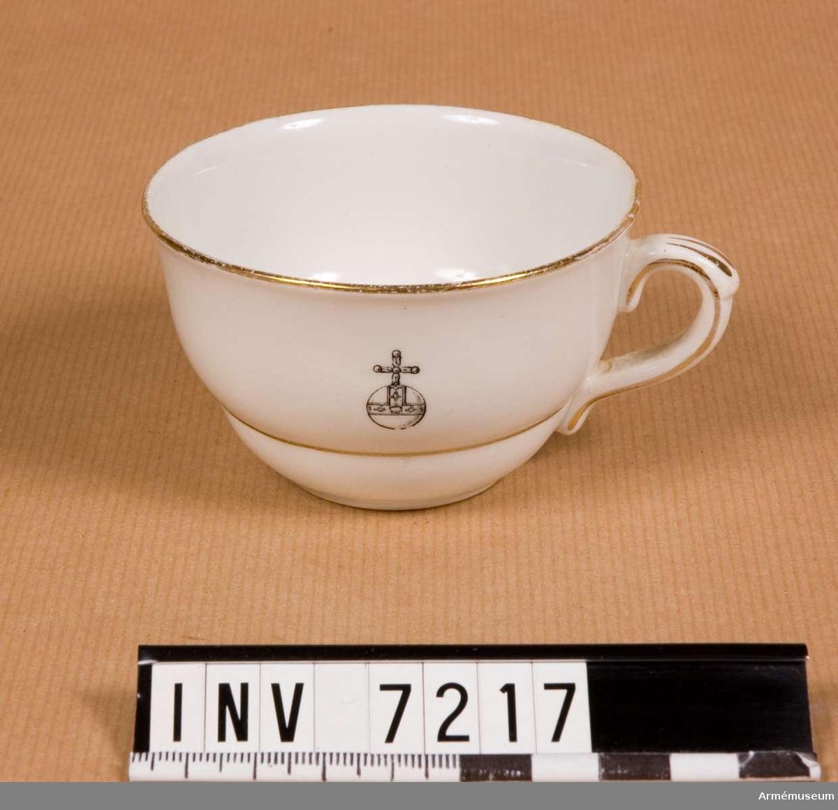 Vit kopp med två tunna ränder i guld. Gulddekor även på hänkeln. Färg vit med guld A, D.