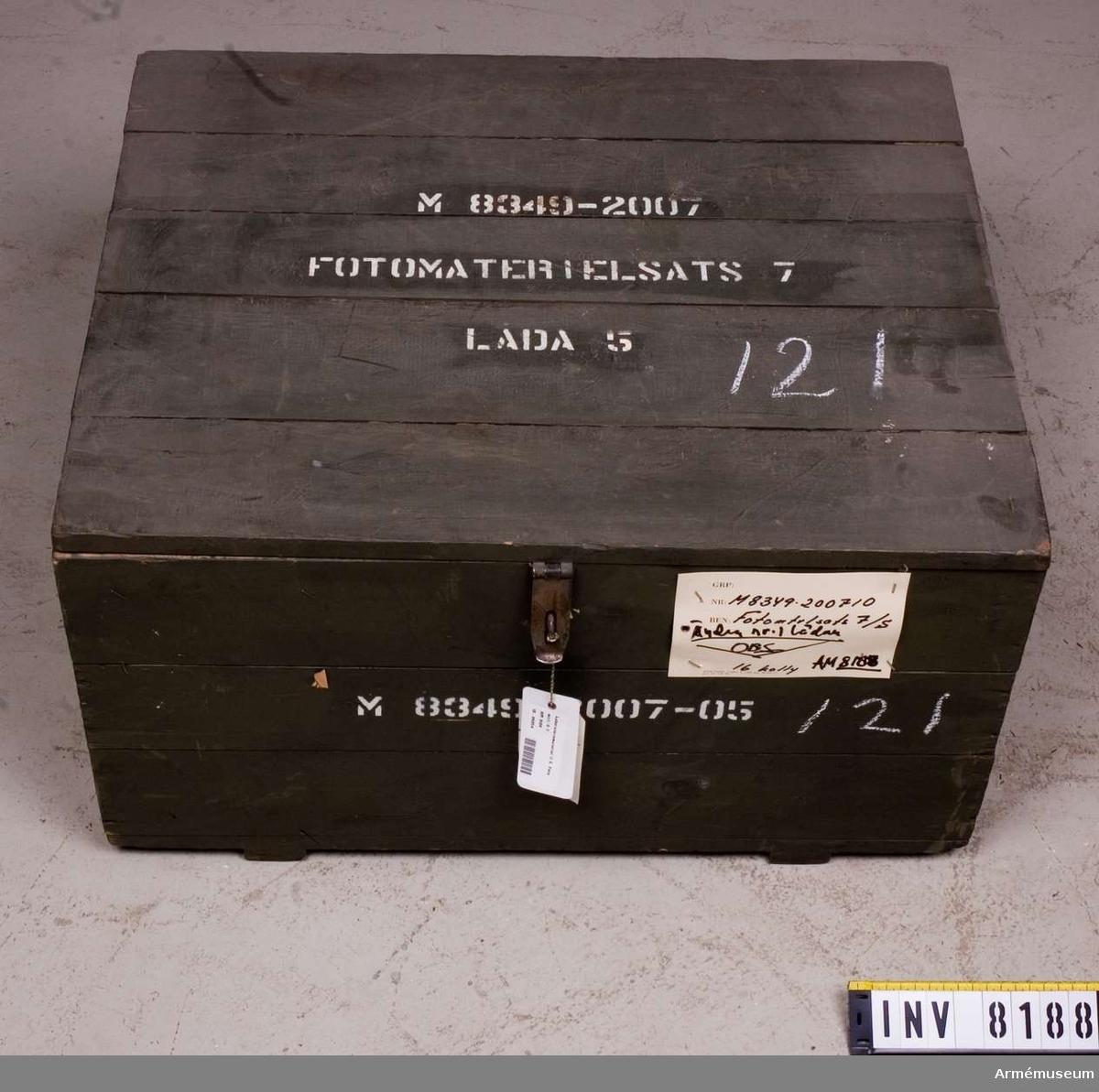 Samhörande nr är AM 8151 - 8199. Färgen är militärgrön.Text på lock och kortsidor: M 8349-2007-05 (Fotomtrl. sats 7. Låda 5). Lådan är till för att förvara förstoringspapper i. Den är tom. Ur fotomaterielsats 7.