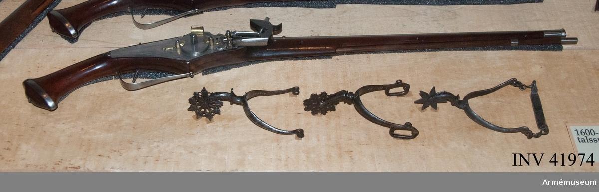 Grupp E III. Hjullåspistol. 1640-50 (troligen något äldre.) /A. Hoff. Pipan är rund med ett 11 cm långt fält med fem grunda och fem djupare längsgående räfflor. Framför nämnda fält finns på pipans översida två ringformade beslag av mässing. Pipan har förstärkt trumf. Låset är av järn med fängpanna och tre mindre beslag av mässing. På låsblecket en stämpel C D B. Stocken är av polerad mahogny med beslag av järn. Kolvkulan är spetsigt oval med ett ringbbeslag. På kolven omedelbart intill svanssruvstjärten en stämpel H G H samt siffran 8. (Stöckel nr c 2871, Thüringen 1650.)