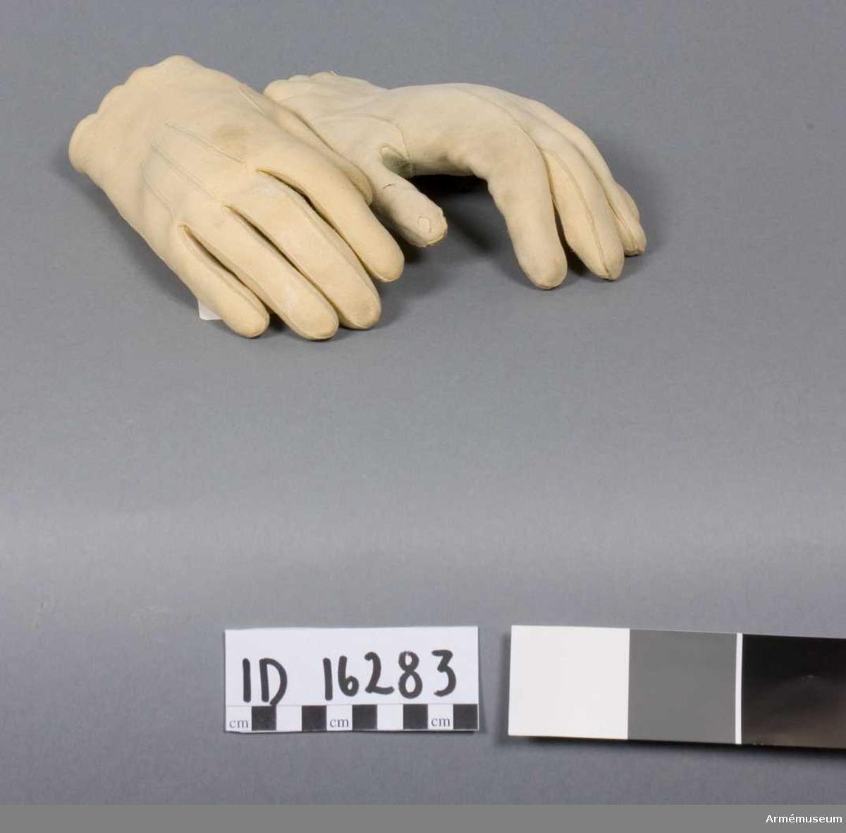 Grupp C 1. Ett par handskar av sämskskinn. Knäpps med en knapp vid varedera handleds undersida.