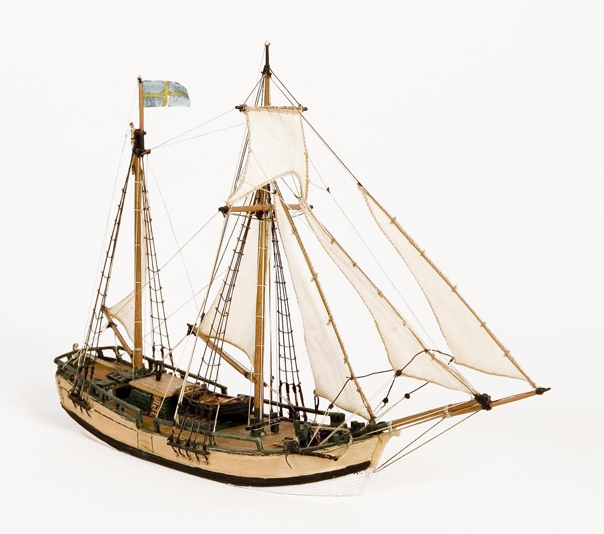 Fartygsmodell på vattenlinje. Galeas, hel i block av trä, med segel av bomull. Skrovet målat ljusgult och vitt i vattenlinjen. Svensk flagga på aktra masten.Föremålets form: Vattenlinjemodell