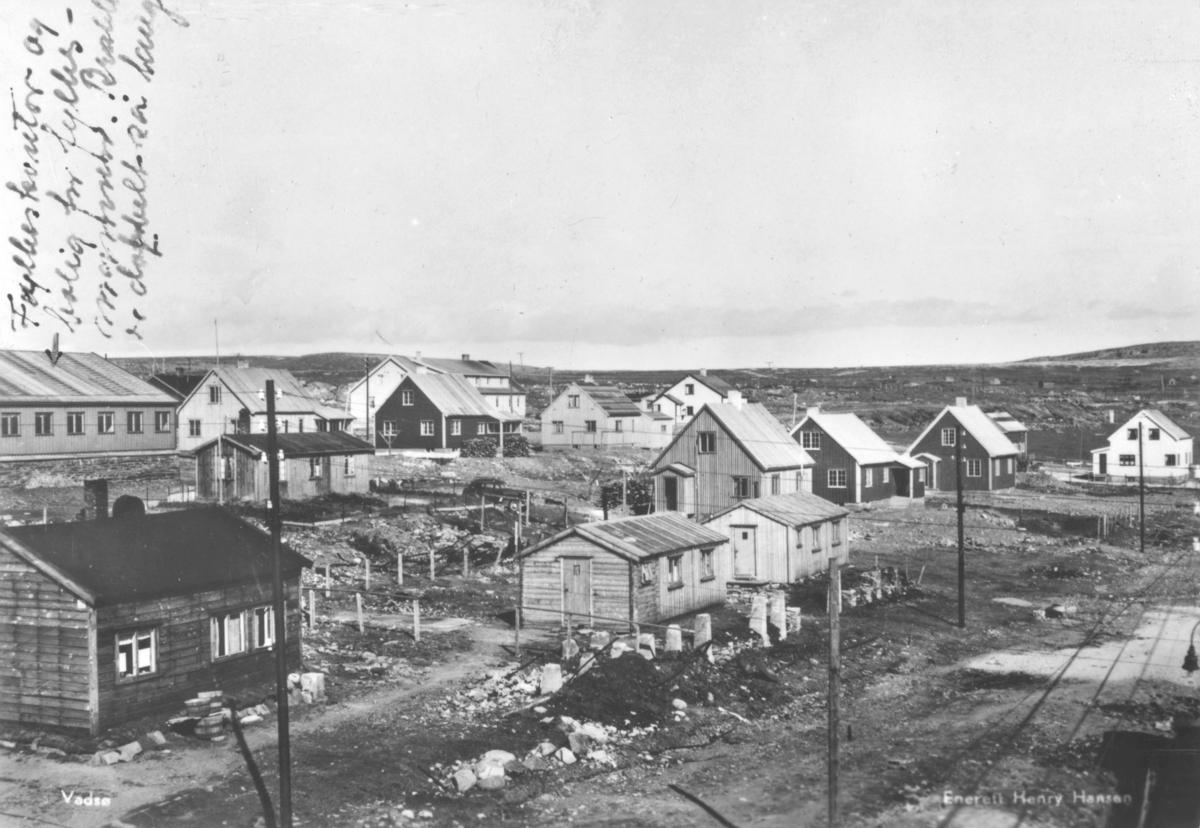 Boliger som er reist etter krigen for gjenreisningsfunksjonærene i Vadsø. Etter hver som administrasjonen ble aviklet, ble husene solgt til private. Disse husene lå i ytrebyen ovenfor R. Esbensen på sletta. De fire brakkene som ses foran i bildet ble satt opp i 1945, og ble revet. Øverst til venstre ses brakken som huset både fylkeskontor og fylkesmannen. Den var dobbelt så lang som det man ser på bildet. I tekst til bildet står det at dette strøket ble populært, eller ikke populært kalt 'bak jærnteppet'