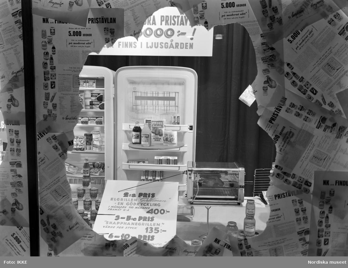 """Skyltfönster på Nordiska Kompaniet. Reklam för Findus djupfrysta livsmedel. """"Var med i NK:s och Findus stora pristävlan ..."""". """"2:a pris elgrillen """"Grillman"""" + en gödkyckling 1 månaden tio månader framåt c:a 400:-. 3-5 pris """"Snapphanegrillen"""" värde per styck 135:-"""""""