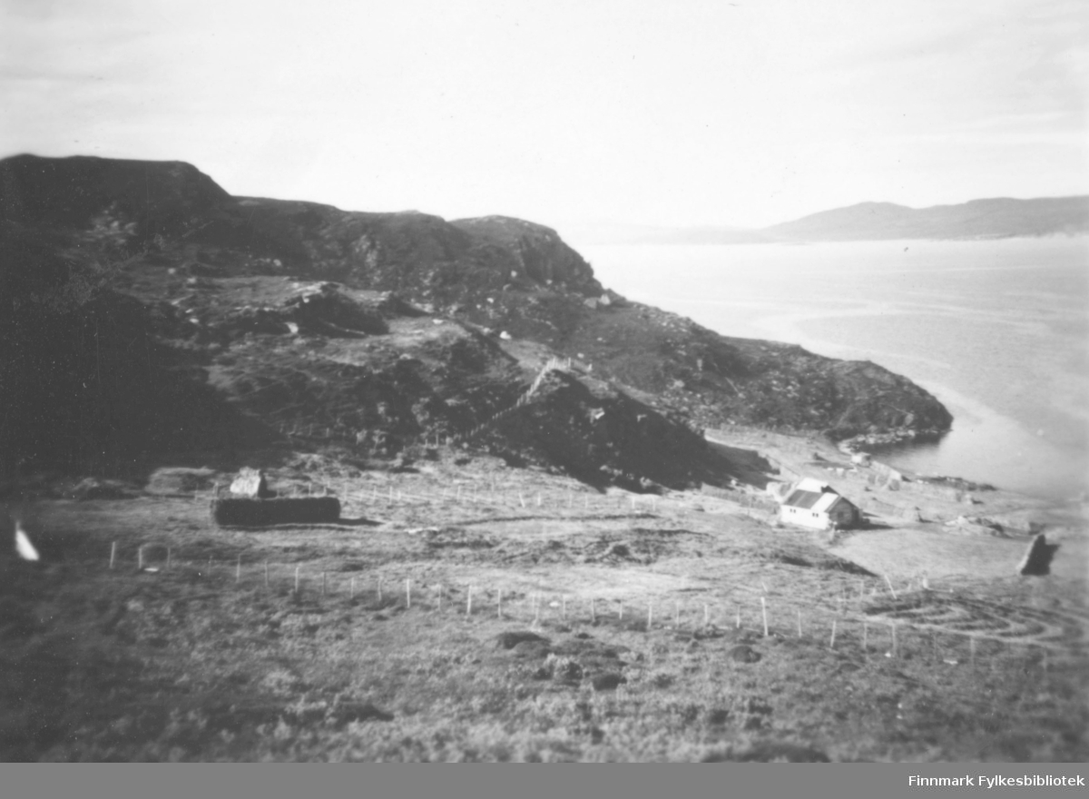 Et gårdsbruk som ligger nede ved sjøen i Storjord. Området er inngjerdet. På hesjene henger det høy