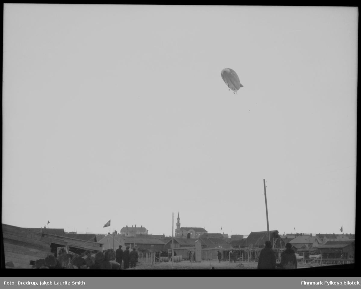 Luftskip over Vadsø med nesen vendt mot Vadsøya.  Vi ser tilskuere som ser opp mot luftskipet.  Bildet er fotografert fra sjøsiden av byen og oppover, og i bakgrunnen ser vi kirka og Amtmannsgården. Vi vet ikke om luftskipet er Italia eller Norge, men det ligger fortsatt mye snø i terrenget over byen, noe som var tilfelle i mai 1926.  Dessuten flagges det over hele byen, og det var mer festivitas over luftskipsferden i 1926.