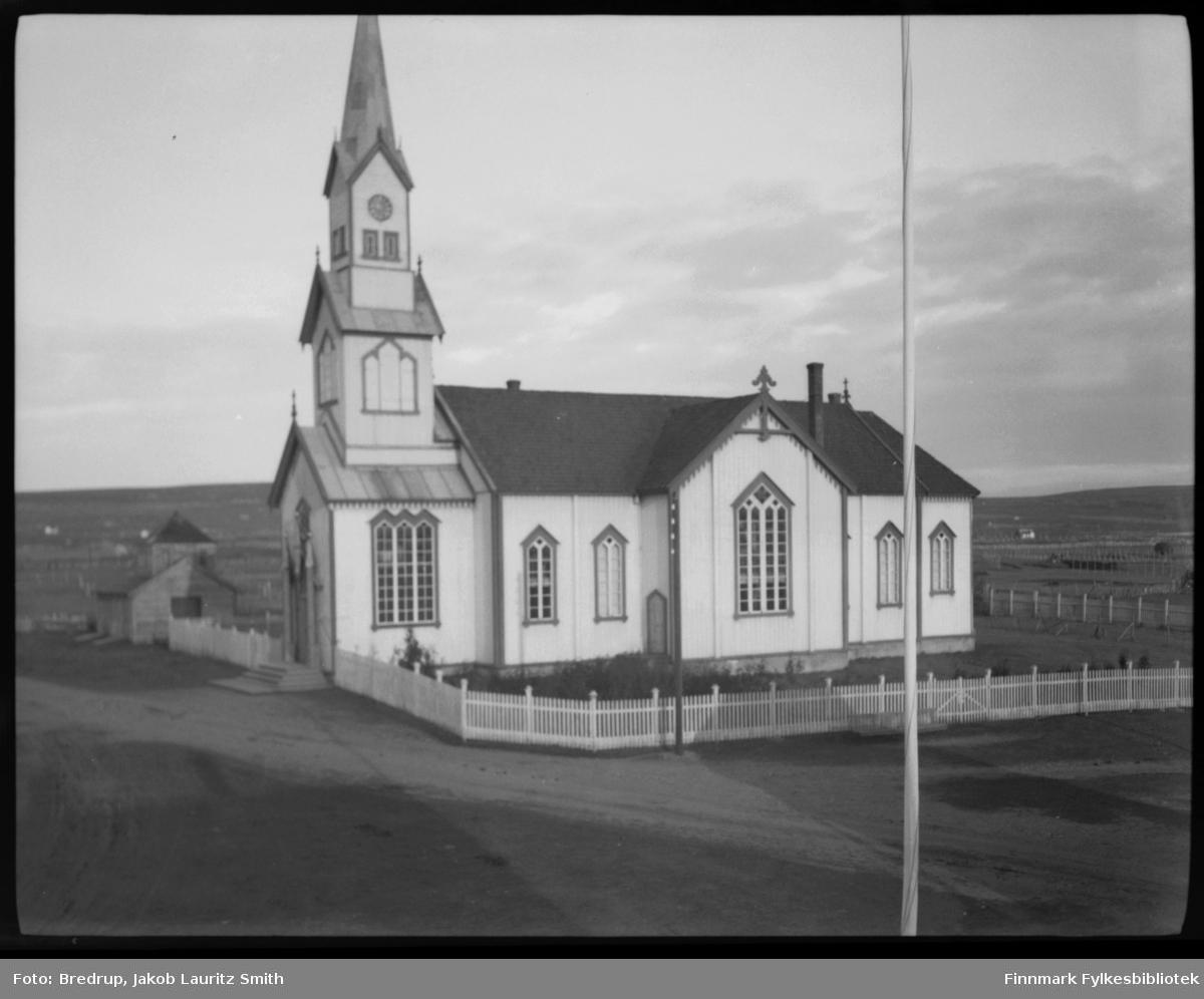 Vadsø kirke med et lite uthus stående til venstre,  Vi ser hagen og stakittgjerdet som omgir kirka.  Tatt fra omtrent samme vinkel som FBib.98012-051, nesten identisk med FBib.98012-053.  Fra Vadsø-kalenderen: 'Vadsø kirke som ble vigslet 3. oktober 1861.  En stilig og rikt utsmykket kirke, som hele byens befolkning var glad i, og der alle store høytider ble markert...Altertavla var en kopi av Adolf Tiedemanns maleri i Trefoldighetskirken i Oslo.  Under tyskernes tilbaketog, natten mellom 28. og 29. oktober 1944, brant kirka ned til grunnen.  Den nåværende Vadsø kirke ble vigslet palmesøndag 1958.'