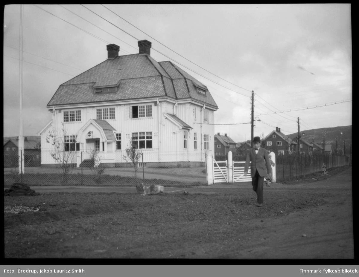 En mann med hatt passerer A/S Sydvarangers administrasjonsbygg i Solheimsveien i Kirkenes.