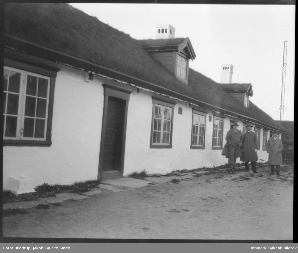 Tre menn fotografert foran garnisonsbrakken, også kalt kasernen eller 'slaveriet', på Vardøhus festning.  Mennene er kledd i hatt og frakk.  I bakgrunnen noe som ser ut som en radiomast.  Bygningen har torvtekt tak med gress, og bygningsdetaljer som vinduer og et par arker på taket kommer godt fram.