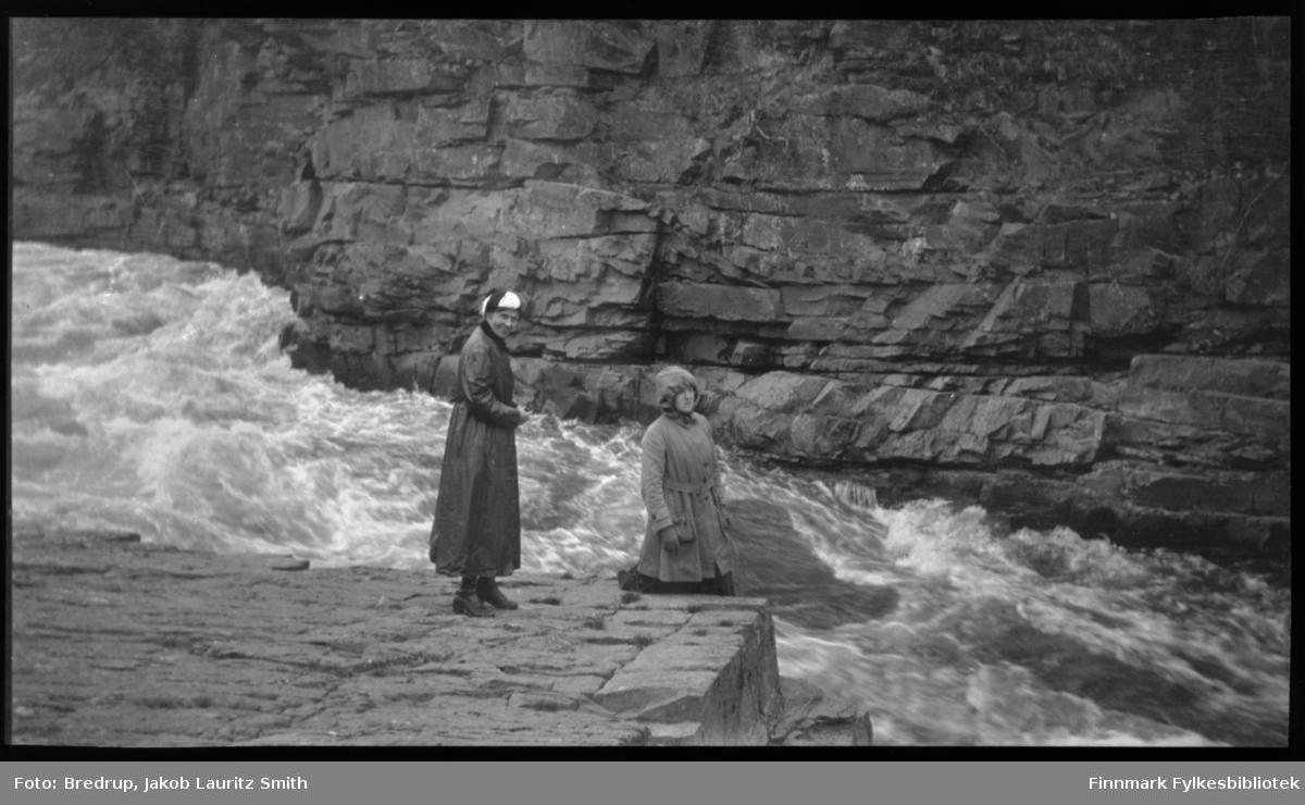 To kvinner i hatt og frakk foran en stri elv, den ene sitter og den andre står.  Kvinnene er ukjente.  Bak elva en steil fjellvegg rett opp.  Vi antar dette er Vestre Jakobselv, fordi så mange andre bilder er tatt i området.