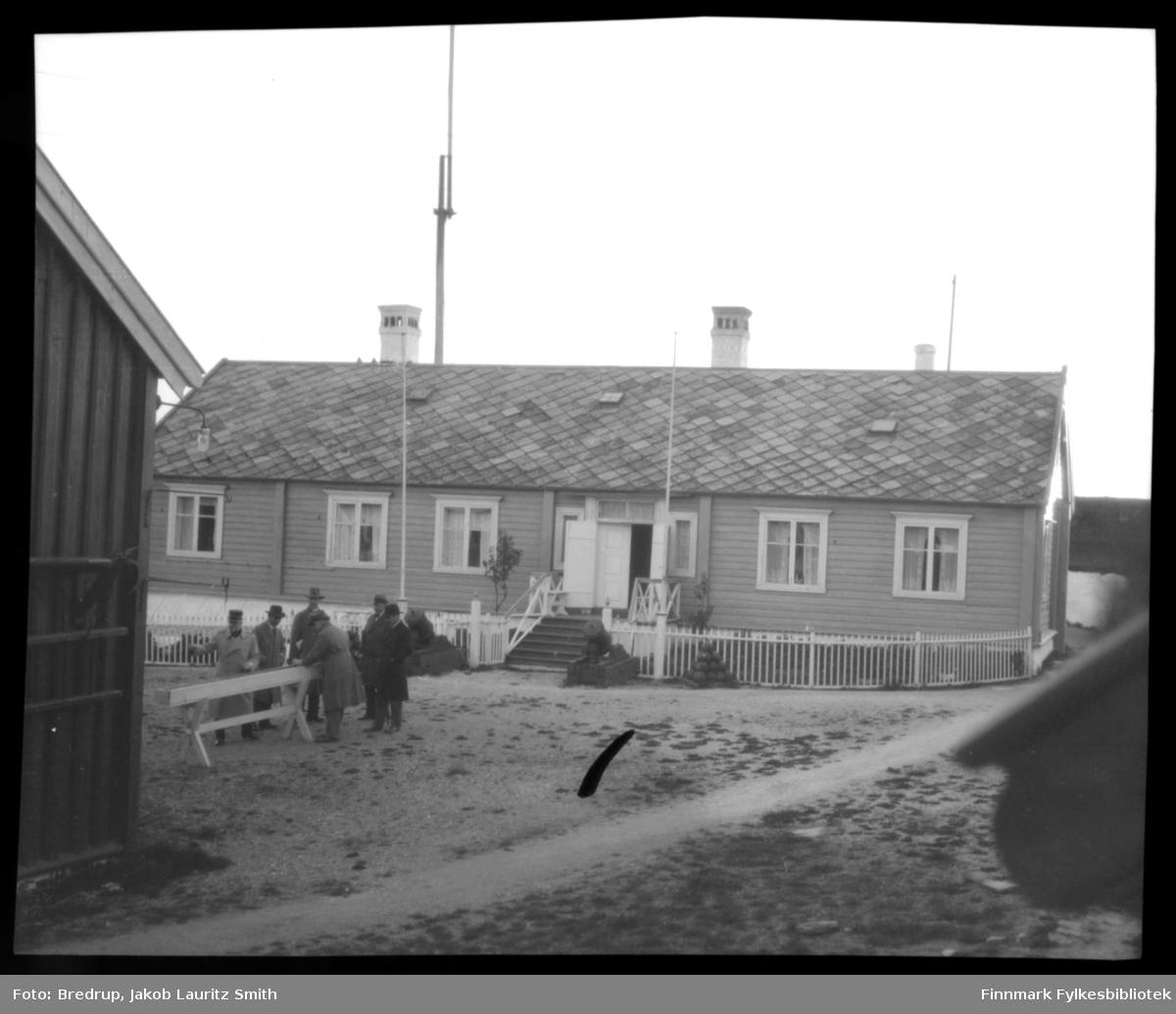 Kommandantboligen på Vardøhus festning.  I fronten pyntekanoner, og Vardøs berømte tre, rogna på festningen.  Seks menn, hvorav en i uniform, ser på kongestokken, som ligger i en egen kasse.