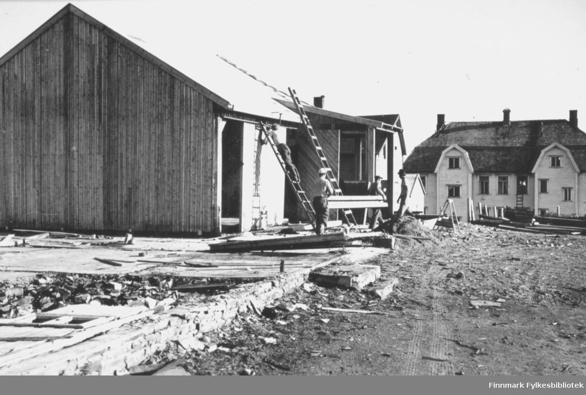 Brakker bygges høsten 1946. Mesteparten av Vadsø sentrum lå i ruiner etter andre verdenskrig, og behovet for et sted å bo var stort. Mange mennesker flyttet inn i midlertidige brakker mens de ventet på å få tildelt bolighus. På dette bildet ser man flere menn som arbeider på bygningen, en står på en stige, to bærer en planke mellom seg, og en fjerde mann befinner seg også i området. I bakgrunnen til høyre ligger Vadsø sykehus