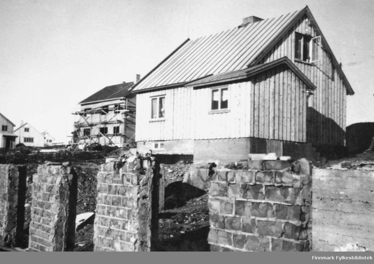 Husbygging i Vadsø sentrum, september 1947. I forgrunnen står restene av en mur. Til høyre i bildet ser man et nybygd hus, og i bakgrunnen et hus under bygging. Bak til venstre står ferdige bygninger