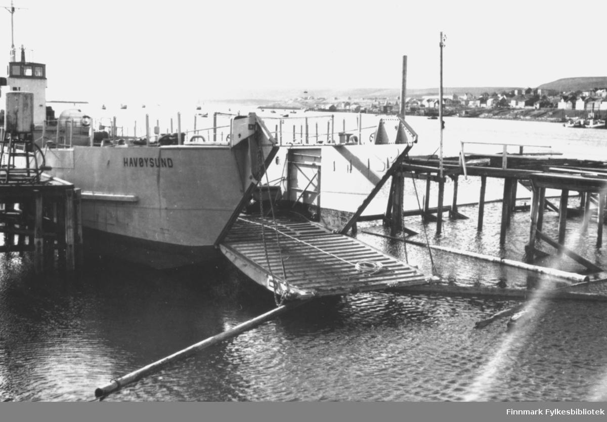 Båten 'Havøysund' ble brukt som lastebåt for å frakte materialer til gjenreisningen av Vadsø etter andre verdenskrig. På dette bildet ligger båten fortøyd ved kaia, med lasteplanet nede. I bakgrunnen ser man deler av Vadsø sentrum