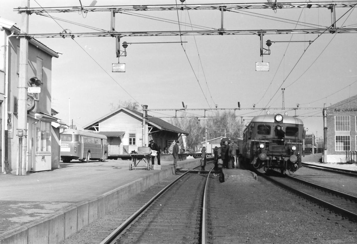 Persontog Charlottenberg - Oslo Ø stopper på Sørumsand. Stasjonsbetjening håndterer ekspress- og reisegods. Buss fra NSB Hølandsrutene. Kryssende tog i bakgrunnen under utkjøring.