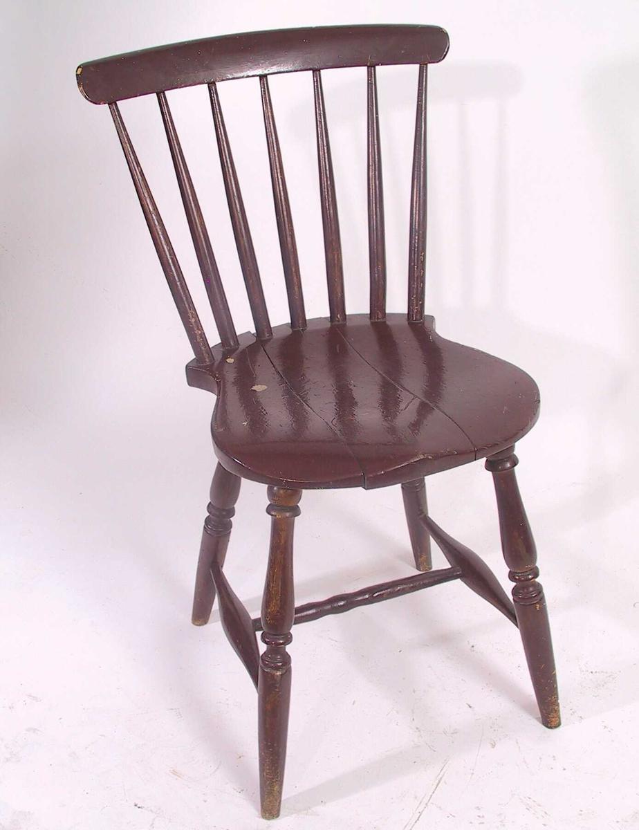 Pinnestol i bjerk,  malt sjokoladebrun.  Utskrådde  dreide  ben, H-kryss. Formet sete, buet ned for lårene i forkant. 7 spiler i ryggen, rundet og buet ryggbrett. Tilstand: god. Under setet påstiftet et stk. finer.