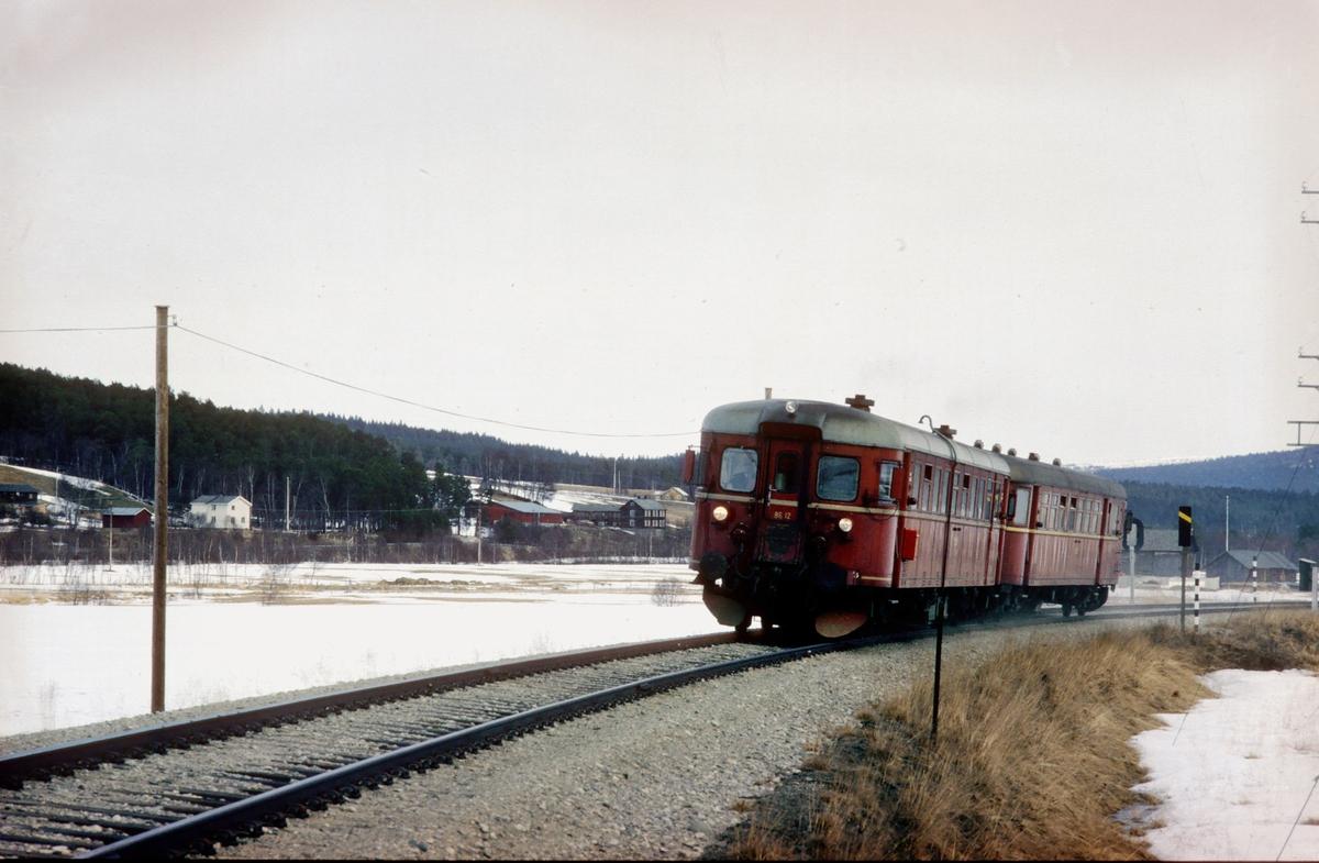 Persontog 372 Røros - Hamar med motorvognsett type 86G. Motorvogn BM 86G 12. Toget hadde på søn- og helligdager ikke betjent postvogn, men postkasse. Ved Bakos planovergang, Os i Østerdalen.
