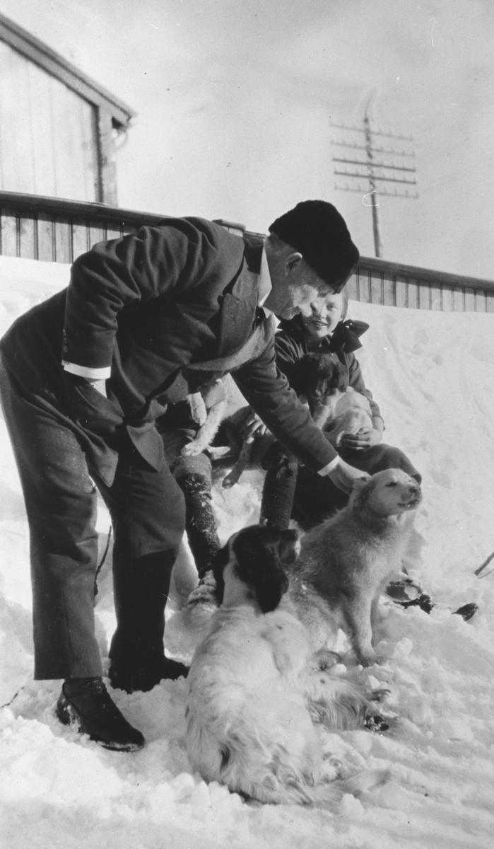 """Vadsø politimester Ludvig Hermansen fotografert på familiens hytte """"Støkke"""" ved Tomaselven i Vadsø sammen med datteren Birgit (""""Biddi"""") og femiliens fire jakthunder påsken 1924."""