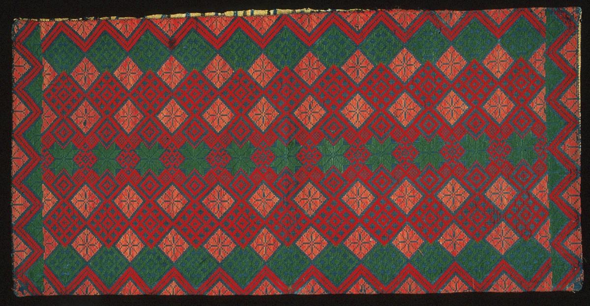 """Bänkdyna/åkdyna vävd i opphämta. Gröna och röda stjärnor samt röda och gröna snedställda rutor på indigoblå botten. Bård i kortsidorna bildas genom förskjutning av mönsterrapporten samt genom färgväxling. Dessutom en sicksack-bård runt om hela dynan. Varp i blått 1-trådigt z-spunnet lingarn, 16 trådar/cm.Botteninslag samma som varpgarnet, 13,5 inslag/cm.Mönsterinslag i 2-trådigt s-tvinnat ullgarn i grönt och två nyanser rött. Baksida vävd i tuskaft med smala ränder i blått, svart, naturvitt och två nyanser gult. Varp i oblekt 2-trådigt s-tvinnat lingarn, 6 trådar/cm. Inslag i 1-trådigt z-spunnet ullgarn, 15 inslag/cm. Fram- och baksida är sammansydda med 2-trådigt lingarn. En 550 mm lång öppning i ena sidan. Märkt på baksidan med påsydd tyglapp med texten: """"Torna h-d  No 250""""."""