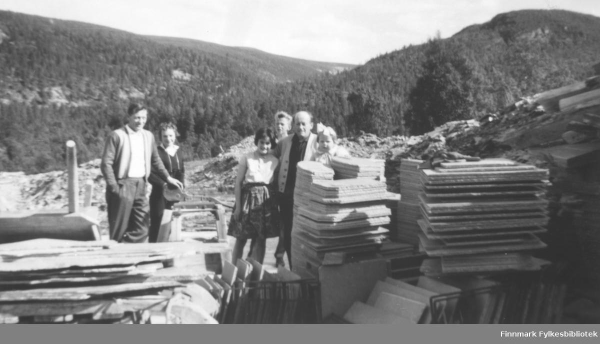 I skiferbruddet i Alta i 1962. Fritz Ebeltoft holder armen rundt datteren Torill. De øvrige er ukjente. Vi ser store stabler med skiferheller i forkant av bildet