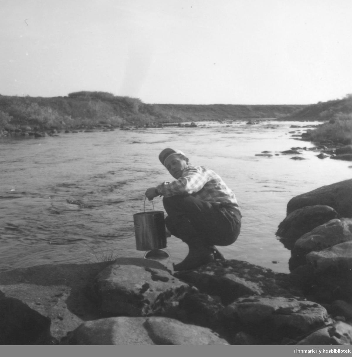 Fritz Ebeltoft henter vann i Ridelva, ca. 1962-1963. Familien hadde hytte i Skallelv