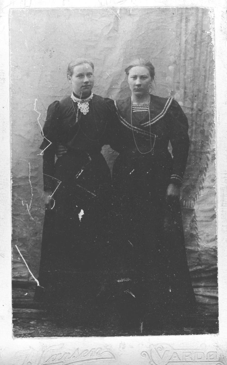 Portrett av to unge kvinner tatt hos fotografen J.Larsen. Kvinnen til venstre ukjent, den andre er Berit Andersen Ingier (f. Amundsen). Hun er kledd i en lang matrosekjole. Kvinnene er fotografert ved en malt bakgrunn.
