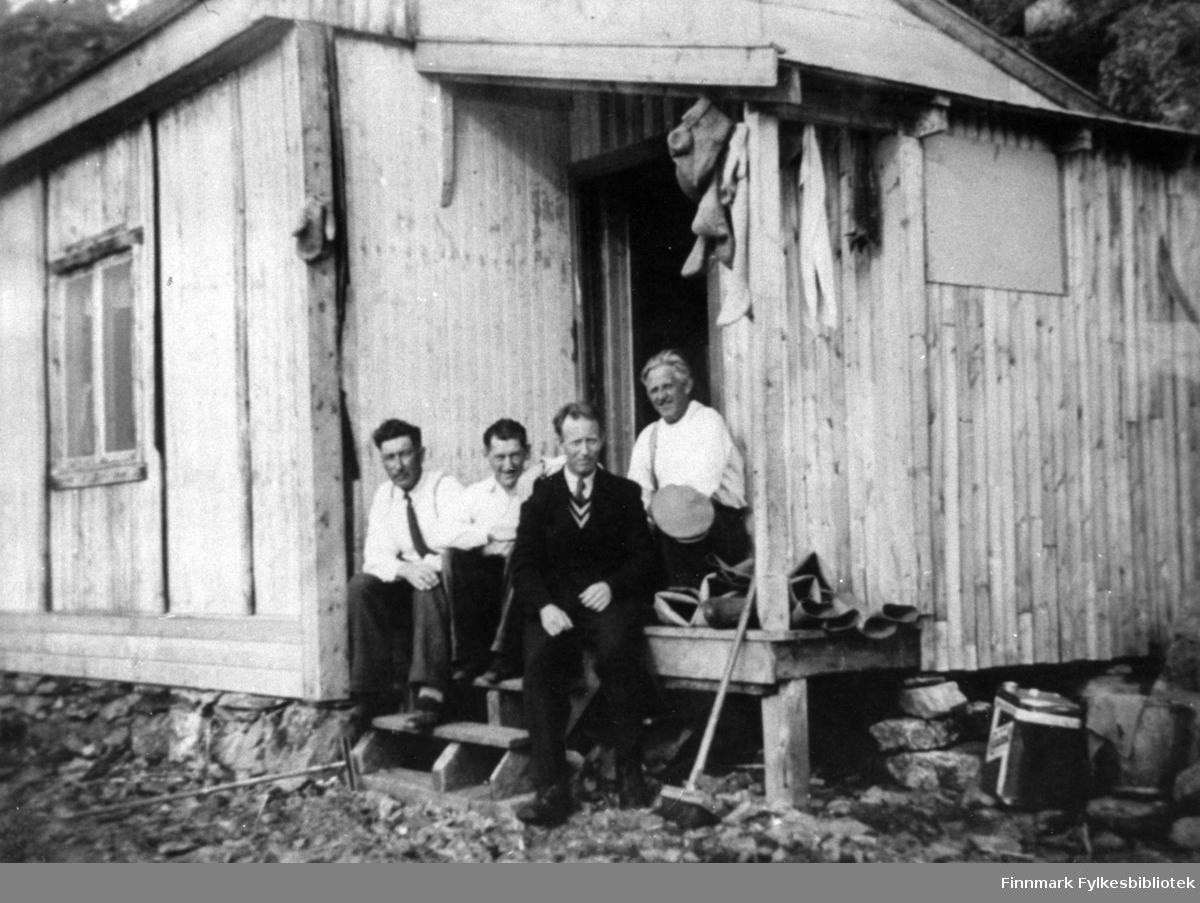 Portrettfotografi av en gruppe som sitter på trappa til en brakke. Fra venstre: Odin Emaus, Odin Nilsen, Agnar Iversen og Håkon Rapp.