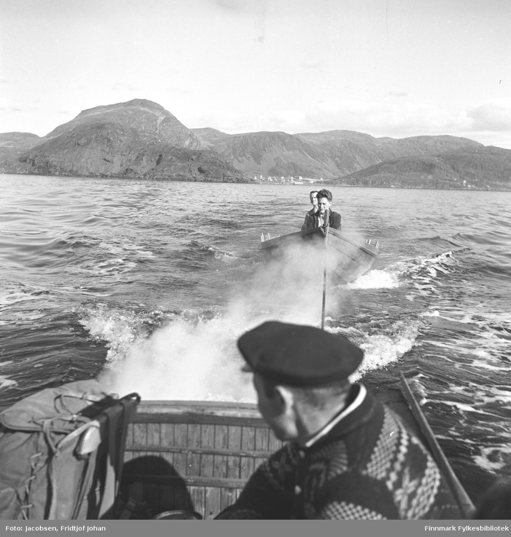 En robåt med to menn slepes av en liten motorbåt i Sørøysundet utenfor Hammerfest og Rypefjord. I motorbåten sitter en mann med strikkegenser, mørk lue og kikker bakover. I bakgrunnen mellom fjellene ligger Rypefjord. Til venstre på bildet ligger Rypklubben med Tyven i bakgrunnen.