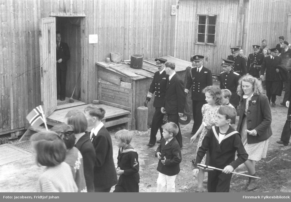 Kongebesøk i Hammerfest 10 juli. Her besøker Kong Haakon VII brakke 9, som var gjenreisningsadministrasjonen. På bildet går Kongen på venstre side av ordfører Toralf Albrigtsen midt på bildet. Bak dem går kongens adjutant og konstituert politimester Arvid Dahl. I døra på brakka står Ernst Moberg. I forgrunnen av bildet går en gruppe barn med festklær og flagg. Jenta helt til høyre er Edith Olsen, og ved siden av henne går Bodil Nilsen datter av Hjalmar Nilsen. Foran dem, i matrosdress, går Bjørn Heggelund. Flere politifolk går et stykke bak Kongen.