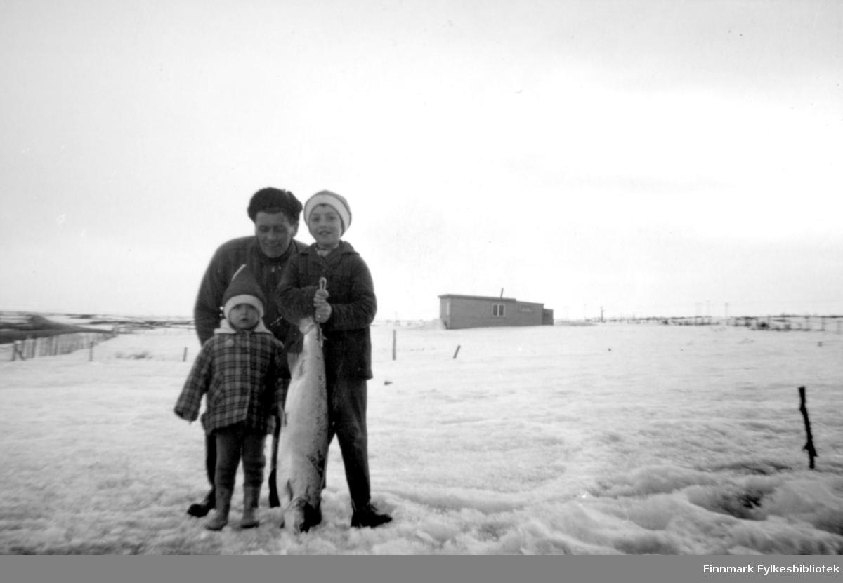Reidar Rushfeldt avbildet med sine to døttre Rannveig og Svanhild Rushfeldt. Laksefisket i havet startet tidlig 1964-65, bildet trolig tatt i slutten av april, muligens tidlig mai. Svanhild holder årets første laks i sine hender og viser den fram til fotografen.  I bakgrunnen kan man se et hus og gjerder. Det er fortsatt sne på bakken.