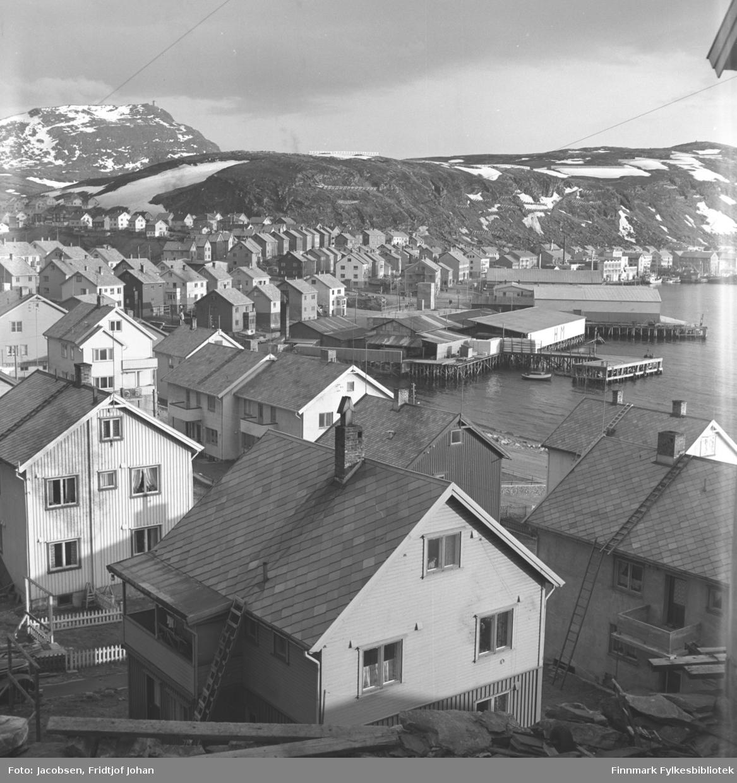 Oversiktsbilde over bydelen Molla i Hammerfest. Husene står ganske tett og feiern har nok meldt sin ankomst siden stiger er reist på flere hus. De fleste husene har skiferdekke på taket. Kaia og bygningene oppe, midt på bildet, er Hauans materialhandel. Rett bortenfor er Gabrielsen-kaia med pakkhus. Bygningene står videre bortover mot sentrum. Fjellet rett ovenfor husene er Salen og oppe til venstre ligger Idrettsveien. Fjellet helt bak, til venstre på bildet er Tyven. En del snøflekker ligger i fjellet som tyder på at bildet er tatt på våren.