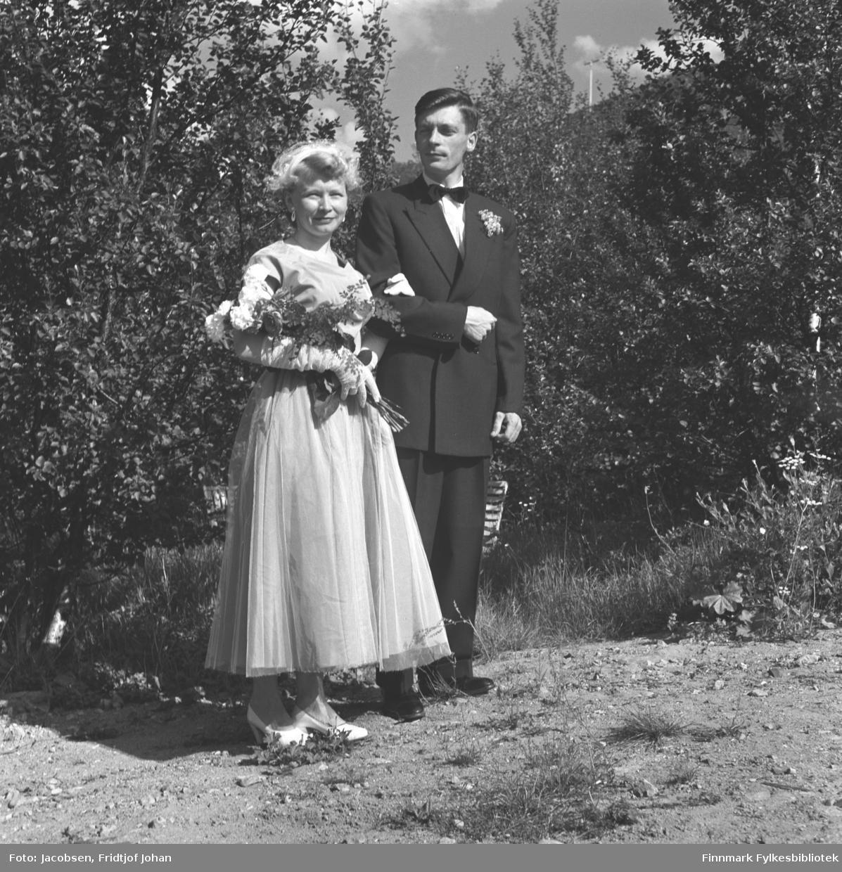 Bryllupsbilde av Øystein Nakken og Henriette Holm. Øystein er Aase Randi Jacobsens yngste bror. Bruden  er iført en ganske lys brudekjole, hårpynt, hvite høyhælte sko og har en stor blomsterbukett på armene. Ved siden av står brudgommen. Han har en sort dress, hvit skjorte og sløyfe i halsen med noe pynt på hans venstre side. Bakken der de står har stort sett grusdekke og mye løvtrær ses rett bak dem. En lys/hvit benk står inne blant trærne. En el-stolpe ses på en fjelltopp oppe til høyre på bildet.