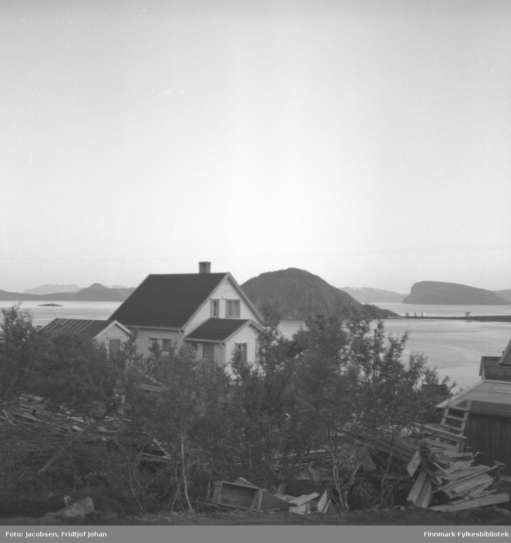 Utsikt mot huset til lærerinne Anna Andersen i Rypefjord, fotografert fra Arne Nakkes eiendom. Det står mange løvtrær foran på bildet og mye treskrot ligger på bakken som planker og kasser. På andre siden av Rypefjorden til høyre på bildet ses Essos tankanlegg på Rypklubbeidet med Rypklubben til venstre. Over tankanlegget ses øya Håja i Sørøysundet. Til høyre på bildet ligger øya Seiland med Rypklubbskjæret foran.