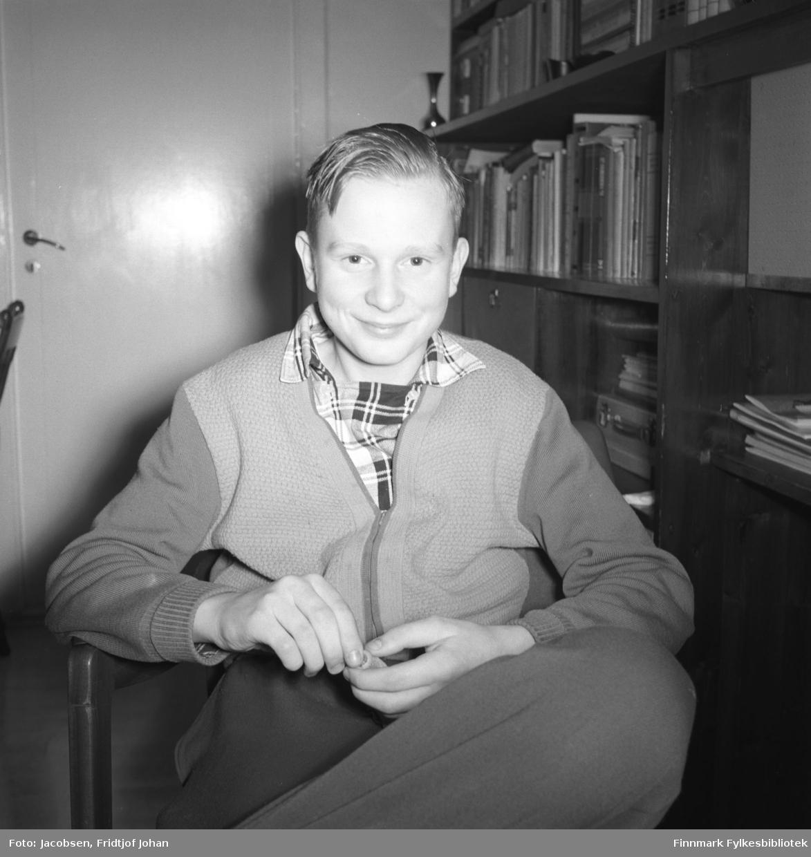 Arne Jacobsen poserer for fotografen. Han sitter i en lenestol iført en ganske mørk bukse, litt lysere genser/jakke og rutet skjorte under. En mørk veggseksjon står langs veggen til høyre på bildet. En del bøker står i hyllene og noen papirer/hefter ligger også der. Til venstre på bildet står en dør som er lukket.