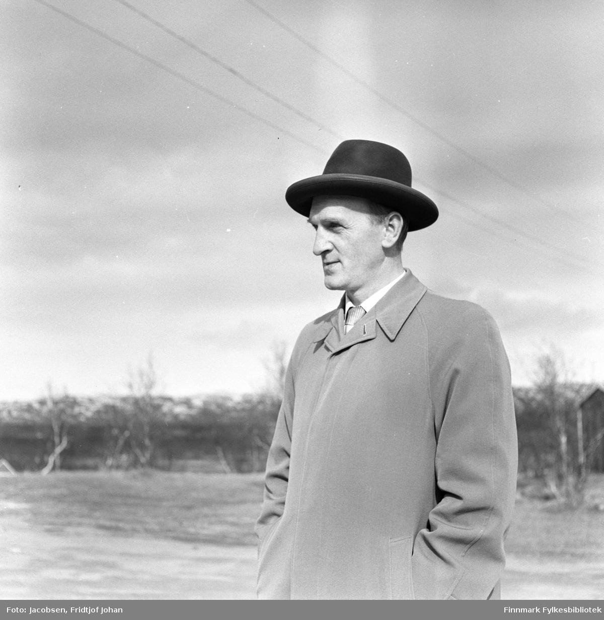 En av Fridtjof Jacobsens kolleger i Televerket, fotografert i nærheten av Lakselv Gjestgiveri. Han er iført en ganske lys frakk og en mørk hatt på hodet. En del trær ses noe diffust i bakgrunnen.