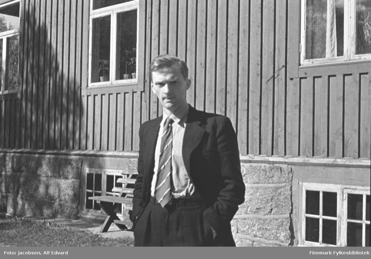 Fridtjof Johan Jacobsen fotografert sommeren 1945 i Lødingen. Han er iført en mørk dress, lys skjorte og stripet slips. Han står med hendene i bukselommene, foran en trebygning med stående panel og grunnmur av stein. Bygningen har 3 tre-delte hvitmalte vinduer på langveggen. Potteplanter og gardiner ses i vinduene. To doble kjellervindu står nederst på veggen, også de med hvitmalte karmer. En trebenk står inntil veggen. En liten flik av gressplen ses nederst til venstre på bildet. Skyggen av et tre ses til venstre på husveggen. Bygningen han står foran kan være huset til familien Kjeldsø på Lødingen.