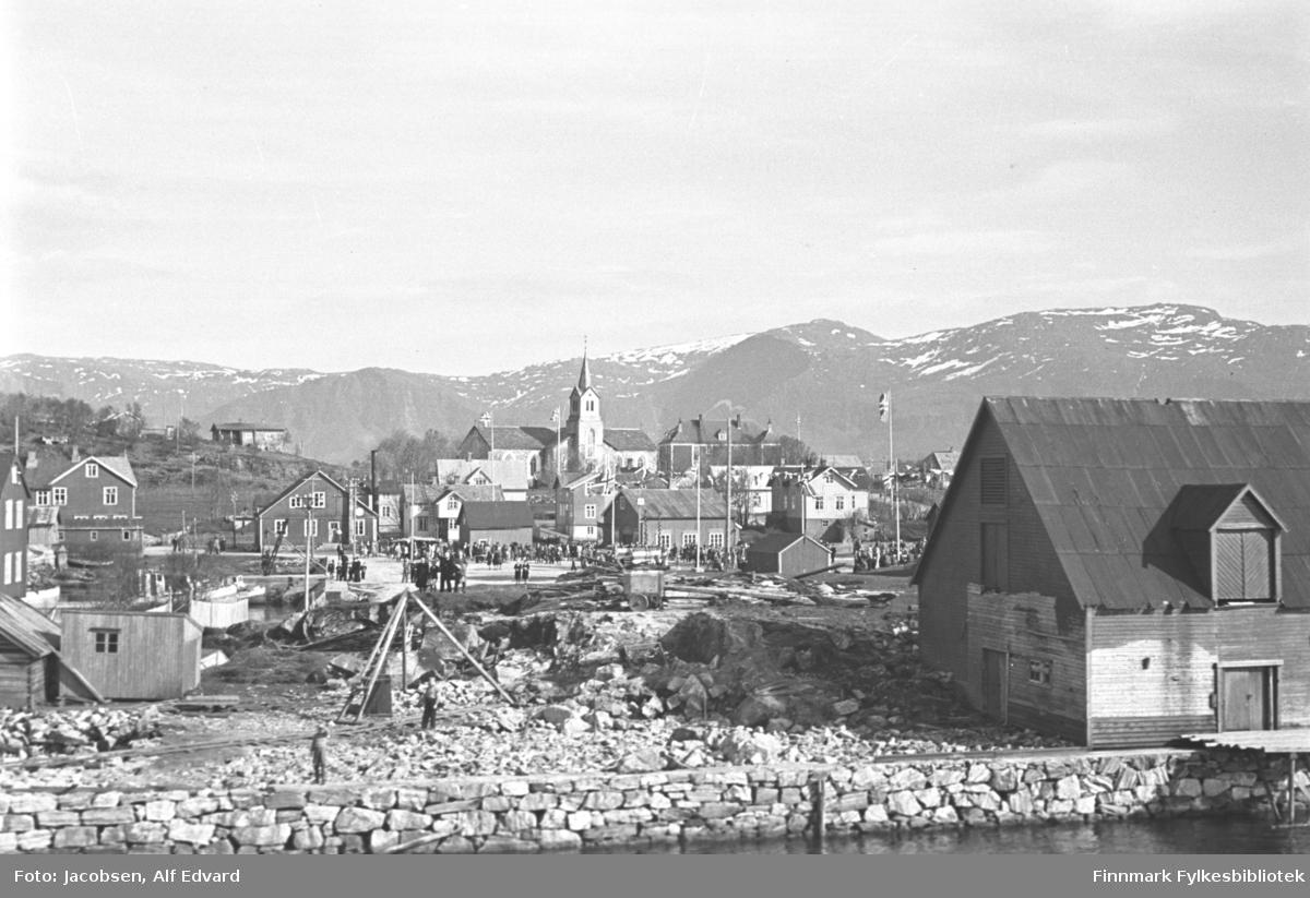 Bilde tatt fra Hurtigruta. Brønnøysund med Brønnøysund kirke midt i bildet.  Et stort pakkhus står nede til høyre på bildet. Kaia bygget står på er murt opp av stein. En liten trekai går ut i sjøen fra langveggen på bygget. To dører/porter ses på veggen og det har papp-dekke på taket. Midt på bildet ses en ganske stor kirke. Det spisse kirkespiret står midt på langskipet. Flere store bygninger/boliger står rundt på området. Flagget er heist på stanga som ses til venstre for pakkhuset og mye folk står ute på en åpen plass midt på bildet. Litt vegetasjon vises helt til venstre på bildet. Snøflekker på fjellene i bakgrunnen, solskinn og bart ellers tyder på en vårdag. Bildet kan derfor være tatt en helligdag i mai.