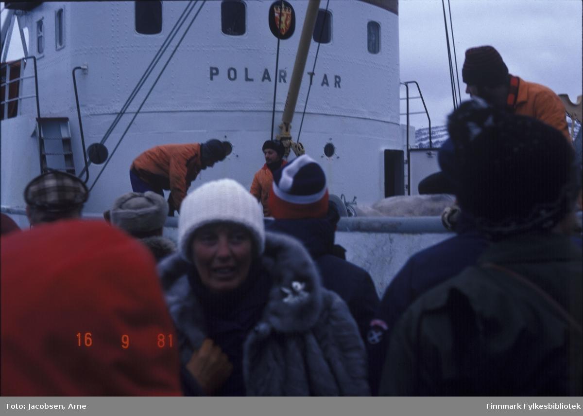 En rekke personer ombord i båten Polarstar. Damen nærmest har pelsjakke og en lys lue på. Alle personene har luer og varme klær på seg. Rorhuset har det norske riksvåpen mellom de fire vunduene. Lastebommen med wire' går fra rorhuset og opp mot baugen. På sidene av rorhuset går trapper opp til dekket bak rorhuset. Bare midten av september, men på fjellet i bakgrunnen kan man se et tynt lag av den første snøen.