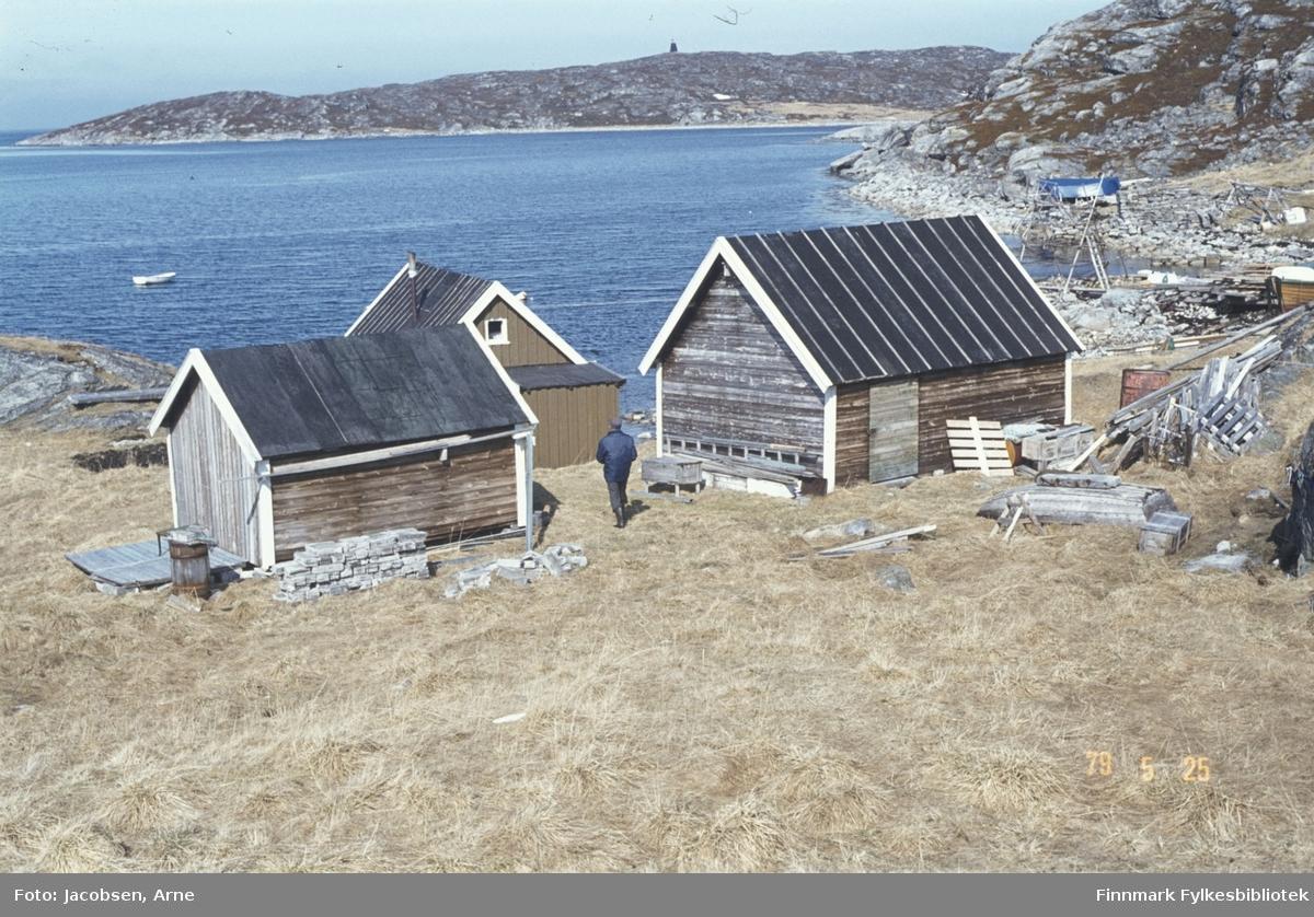 Tre båthus/små bygninger langs fjæra, muligens i Sandbukta i Forsøl. En person med ganske mørke klær går mellom bygningene. Det er mye gress i området, men til høyre er det endel stein og lyng. Ved steinene i fjæra ligger det noe drivved. Paller og annet treverk ligger på området og en kasse ligger på bakken til høyre på bildet. De to nærmeste bygningene har liggende panel og papp på taket. Nederste har stående panel, et lite tilbygg og papp på taket. En lettbåt ligger fortøyd ute i bukta og på andre siden av bukta ligger, sannsynligvis, Forsølholmen med et sjømerke på toppen.