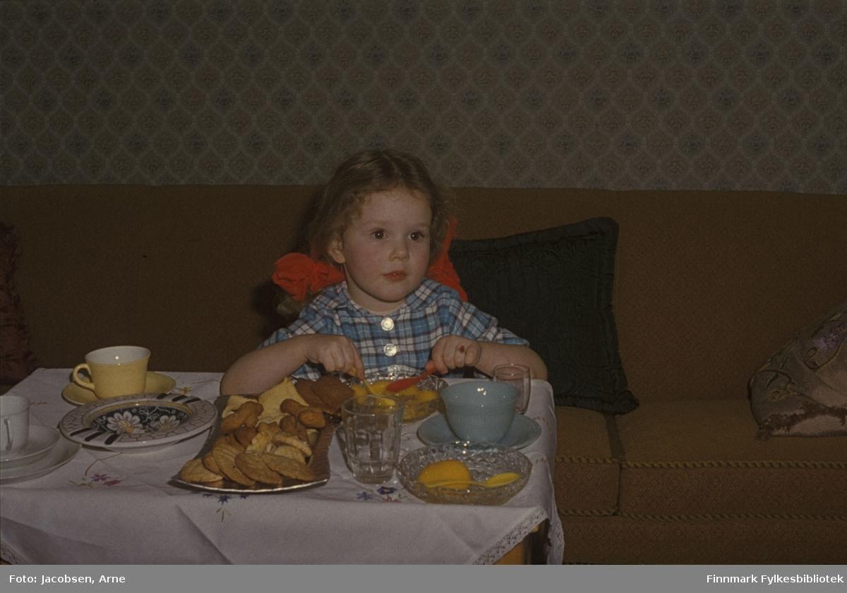 Ranveig Jacobsen sitter i sofaen og spiser kake. På bordet står kaffekopper med tefat og asjett. Hun har en kortermet, rutet skjorte på. To glass og et brett med kjeks og småkaker står også på bordet. En stor, lys duk er lagt over bordet. Tre puter ligger i sofaen.