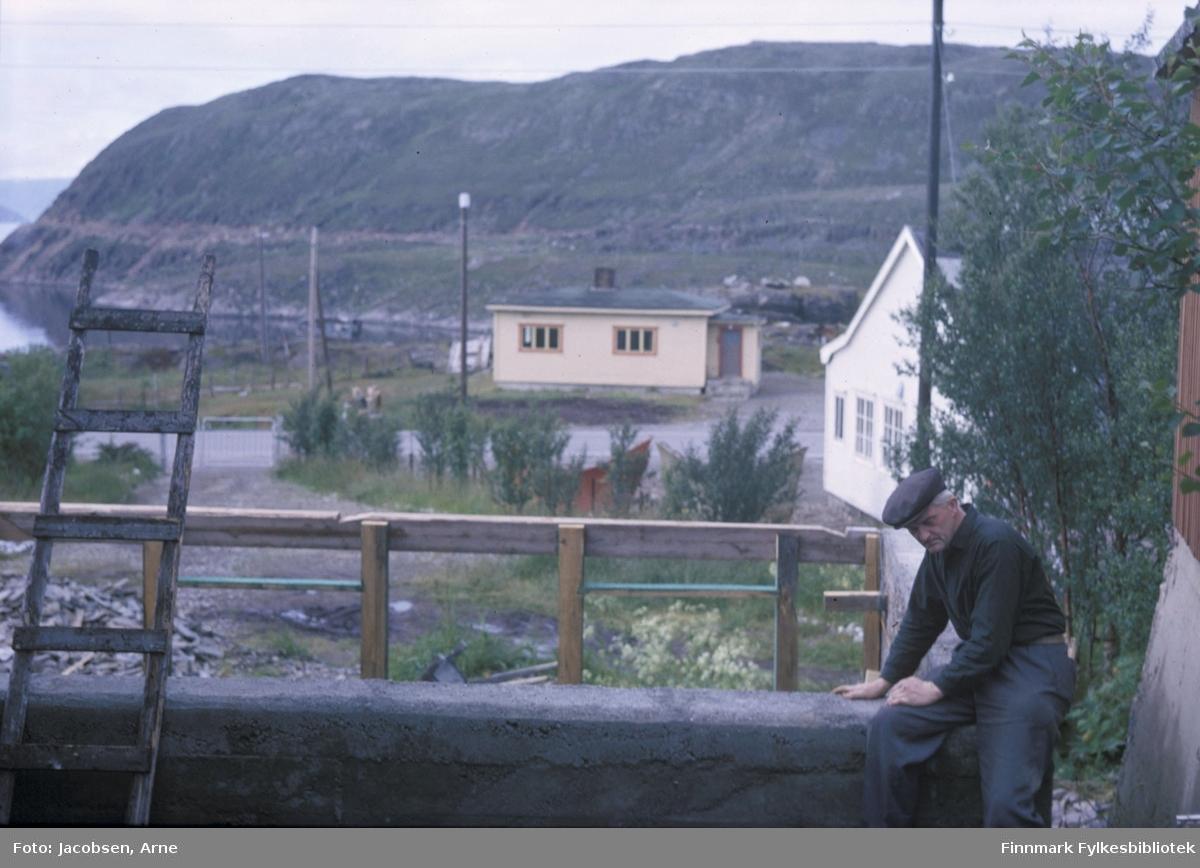 Fridtjof Jacobsen sitter på muren til bygget han holder på å reise i Bjørkåsen 4, Rypefjord. Han har mørk skjorte, bukse på og sixpence på hodet. En trestige står oppreist mot muren og flere lykte- og strømstolper ses. Et lite hus midt på bildet på andre siden av Fjordaveien. Røstvegggen på et større hus ses bak noen trær med løv til høyre på bildet. Noen trær står langs oppkjørselen til bygget. I bakgrunnen står Rypefjell med Rypklubbveien langs fjellet. En blikkstille Rypefjord ses såvidt oppe til venstre.