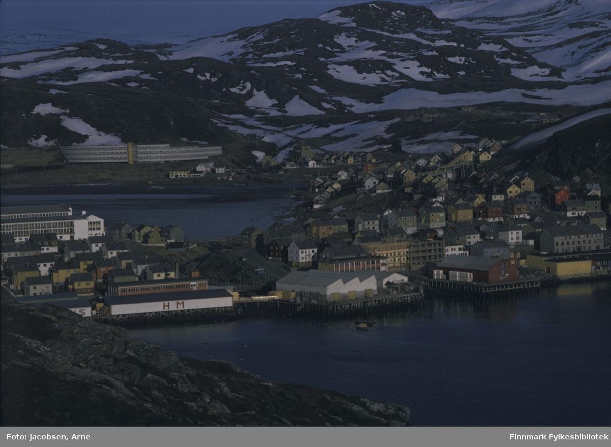 Del av Hammerfest sett fra Fuglenesfjellet. Bygget fremst, til venstre med HM malt på veggen, er Hauans materialhandel med butikk og lager på kaia midt i bildet. Vi kan såvidt skimte Storelva renne fra Storvannet og ned i havnebassenget. Til høyre for Hauans, med kasser stablet opp langs veggen, står et pakkhus/lager på Gabrielsen-kaia. Del av Findus ses i strandkanten til høyre og rett ovenfor står St. Elisabeth-bygningen. Midt på bildet, til venstre ses Breilia skole og nedenfor boligområdet Molla. Den karakteristiske Hesteskoblokka, på folkemunnet kalt Bybo, står ovenfor Storvannet. Fra høyre side av Storvannet og videre oppover ser vi boliger i Idrettsveien-området. Fjelltoppen midt på bildet er Sukkertoppen. Det er en del snø og snøflekker så bildet er nok tatt på våren.