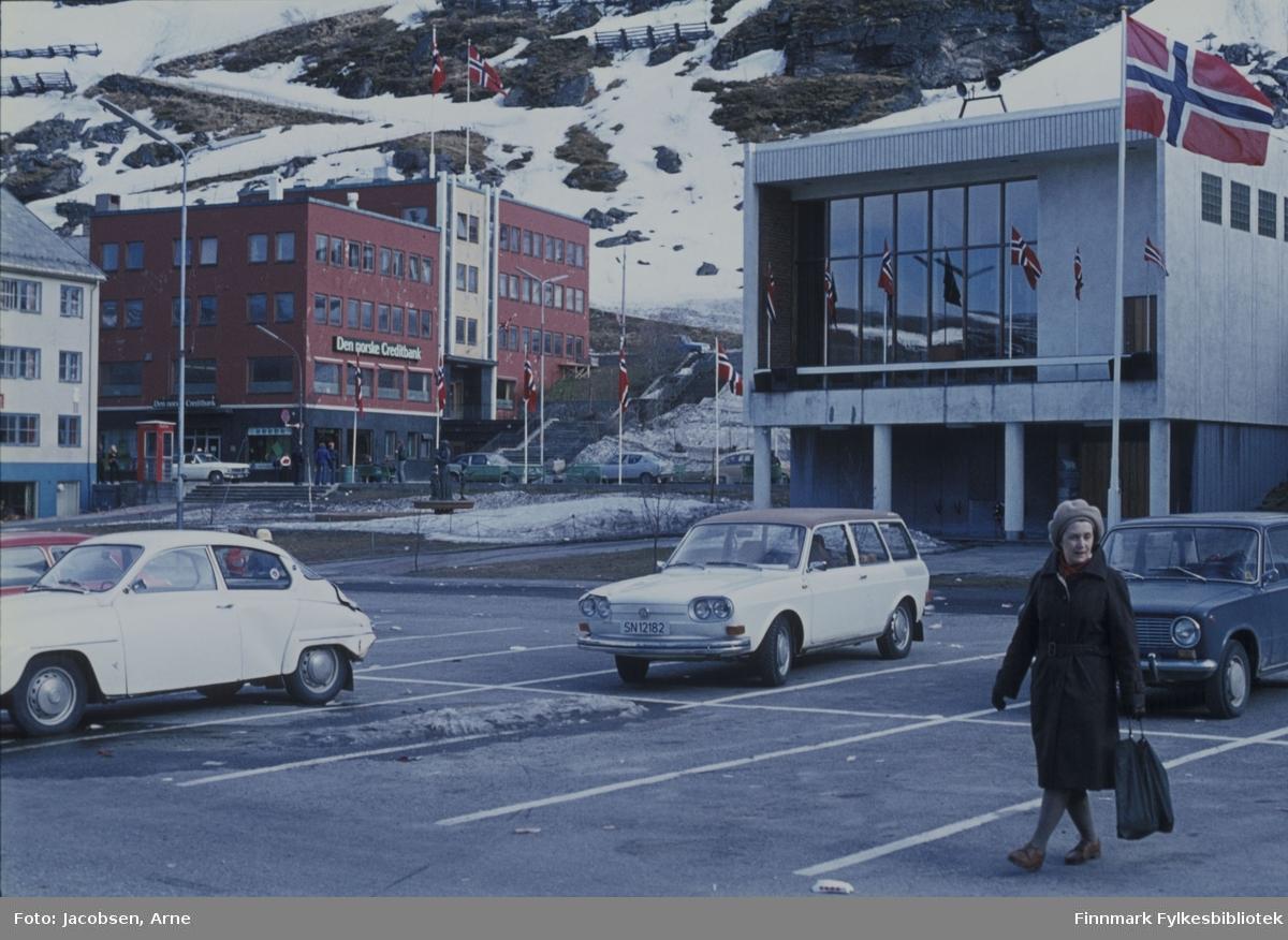 Aase Jacobsen på Rådhusplassen i sentrum av Hammerfest. Hun har en mørk kåpe, lue og hansker på. Strømpebukse og lavhælte sko. Hun bærer på et nett og 3 biler står parkert, en Sabb, en VW og en Lada. Rådhusplassen  er bar og har oppmalte parkeringsplasser og et flaggprydet rådhus bak henne. En del snø ligger i Salsiden, på Ole Olsens plass bak rådhuset og i parken ved fontenen. I Salsiden står noen snøskjermer og Sikksakk-veien opp fjellet er begynt å tines fram. Flagg er også heist på stengene i parken. Noen biler kjører i Strandgata og noen mennesker ses på fortauet.  Bygget helt til venstre er Finnmarksbo, og ovenfor det ligger DnC-bygget