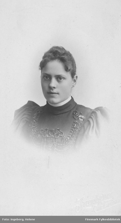 Portrett av ukjent kvinne. Hun er kledt i mørk kjole eller bluse som det er festet et stort smykke på