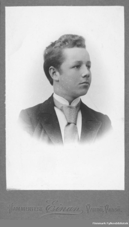 Portrett av ukjent ung mann. Han er kledt i en mørk jakke og hvit skjorte. I halsen har han et slips