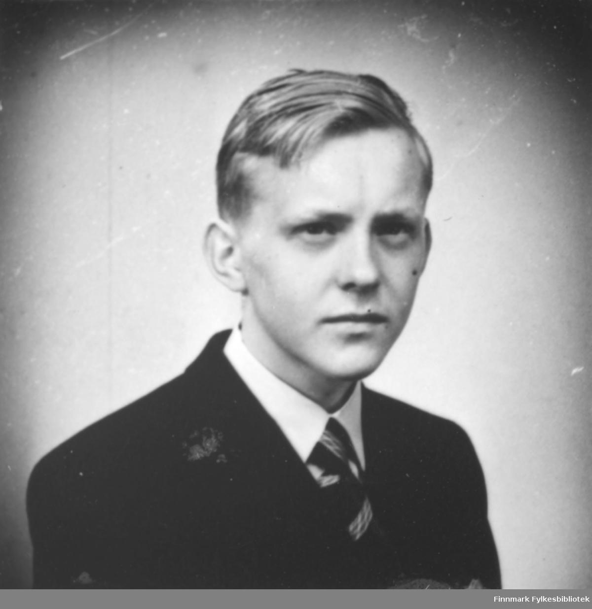 Portrett av Per Vibe Jacobsen f. 1932 i Bergen. Sønn av August Magnus Jacobsen og sønnesønn til smedmester i Vardø Ole Sigfrid og hustru Anna Christine Jacobsen. På bildet er han kledt i mørk jakke og hvit skjorte. I halsen har han et slips