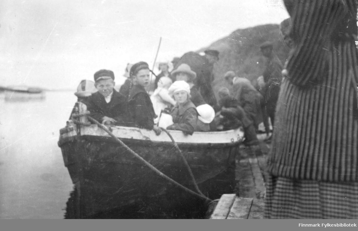 Fotografi av en åpen trebåt som ligger fortøyd på en ukjent plass. Det er både menn, kvinner og barn ombord. Alle er ukjente. Det står en dame og noen menn på kaia. Vannet er blikkstille